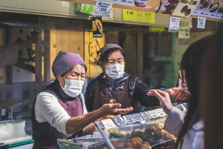 women exchanging food and money at an outdoor street market while wearing masks