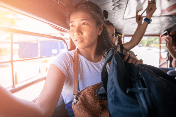 Woman gazing out the window of a jeepney (bus) while holding a backpack